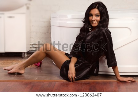 Beautiful brunette spa woman sitting on the floor in the bathroom
