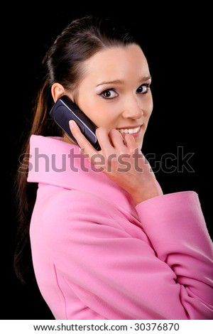 Beautiful brunette talks by mobile phone, is isolated on black background.