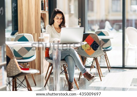 Beautiful brunette using notebook in cafe #435009697