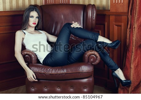 Beautiful brunette wearing tight jeans, resting on an armchair in a luxurious apartment.