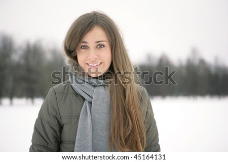 Beautiful brunette winter on the street looks into the distance and laughs