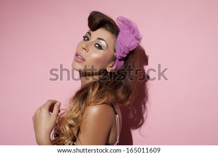 Beautiful brunette with a purple hair ornament posing sideways looking seductively at the camera against a pink studio background #165011609