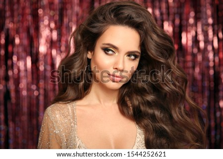 Beautiful brunette with Healthy wavy hair. Glamour Makeup. Fashion Beauty Girl with carnival mask Isolated on bright bokeh Christmas lights Background.  Gold Jewelry copy space. Hairstyle.