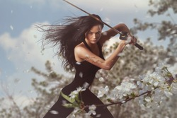 Beautiful Brunette with katana sword in spring floral environment