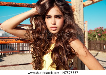 beautiful brunette with long wavy , shine hair and fresh make up posing on a sunny day. Horizontal summer street shot.