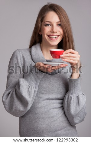 Beautiful brunette with red cup of coffee