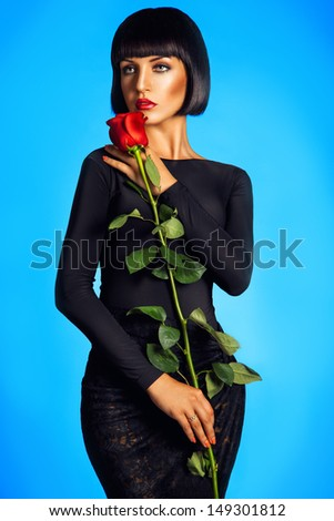 Beautiful brunette with red rose on blue background