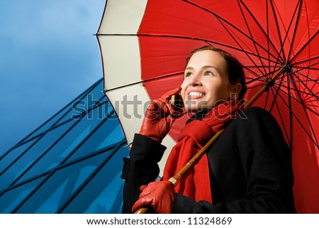 Beautiful brunette with red umbrella talking on the phone - stock photo