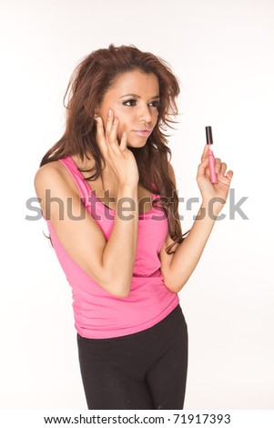 Beautiful brunette woman applying pink lipgloss , make-up preparation on white