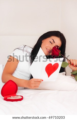 beautiful brunette woman at home was a gift from a loved one, postcard, heart and roses. feast day of St. Valentine