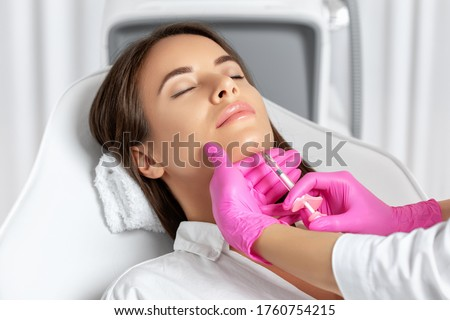Beautiful brunette woman at the beautician.Cosmetologist does anti wrinkle injections on the chin against sagging skin. Women's cosmetology in the beauty salon.