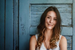 Beautiful brunette woman boho style, white top, sombre ombre hair, turquoise background, turquoise door structure, smiling, looking, happy, curly brown hair