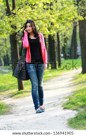 Beautiful brunette woman calling on the phone outdoor in the park