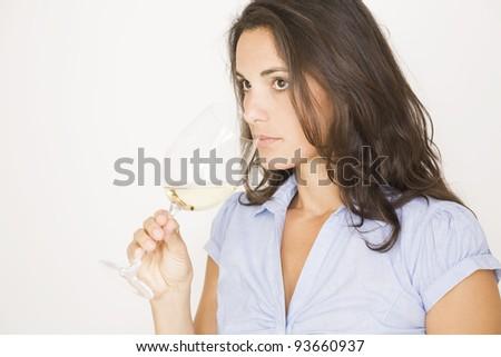 Beautiful brunette woman drinking a glass of white wine - stock photo