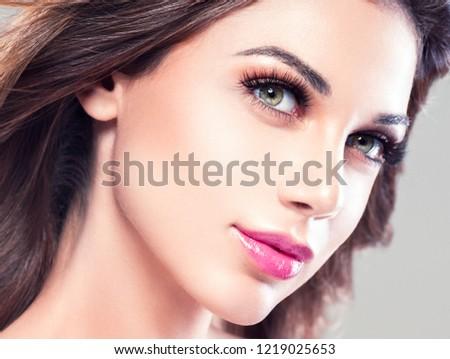 Beautiful brunette woman face closeup beauty eyes and lips makeup female portrait #1219025653