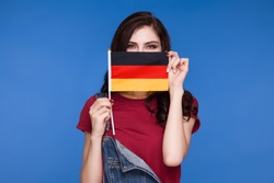 Beautiful brunette woman holding a flag of germany in her hands and covering her mouth, on a blue background. Learning German. Travels.