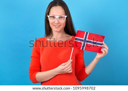 Beautiful brunette woman holding a flag of Norway standing in front of a blue background.
