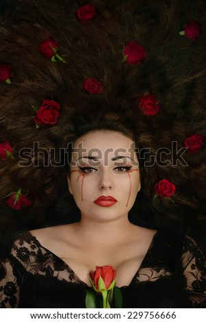 Beautiful brunette woman holding rose and with roses in her hair crying blood. Fantasy woman. Book cover