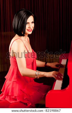 beautiful brunette woman in red dress playing piano