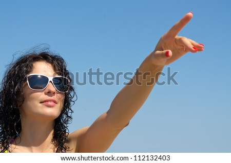 Beautiful brunette woman in sunglasses pointing with her finger up into the blue sky - stock photo