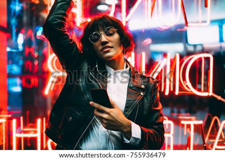Beautiful brunette woman in trendy apparel and eyewear enjoying nightlife in city listening music in earphones and moving to sound, gorgeous hipster girl dancing outdoors on neon city illumination