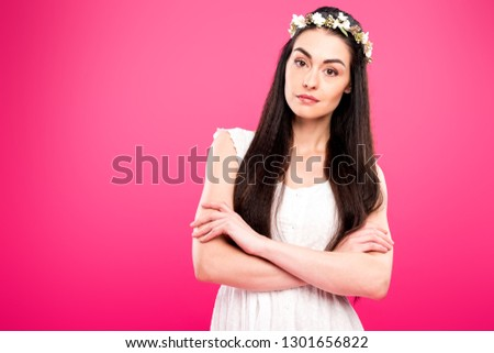 beautiful brunette woman in white dress and floral wreath standing with crossed arms and looking at camera isolated on pink #1301656822