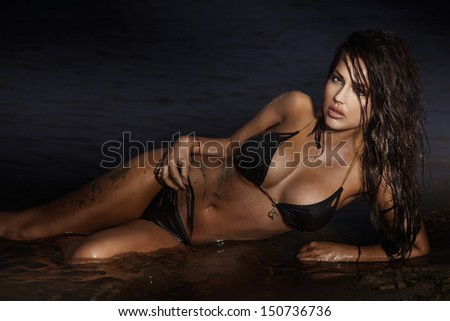 Beautiful brunette woman lying and relaxing on the beach.