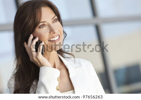Beautiful brunette woman or businesswoman in her thirties talking on a cell phone.