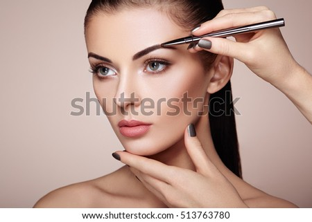 Beautiful brunette woman paints the eyebrows. Beautiful woman face. Makeup detail. Beauty girl with perfect skin #513763780