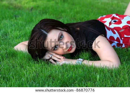 Beautiful brunette woman relaxing in the grass.