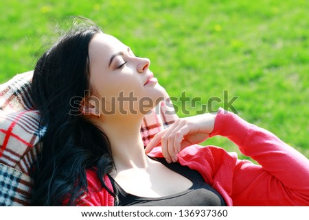 beautiful brunette woman relaxing on lounger in the spring grass enjoying the sunlight
