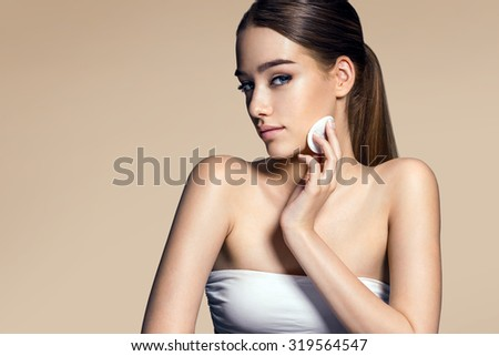 Beautiful brunette woman removing makeup from her face, skin care concept / photo composition of brunette girl with beige background