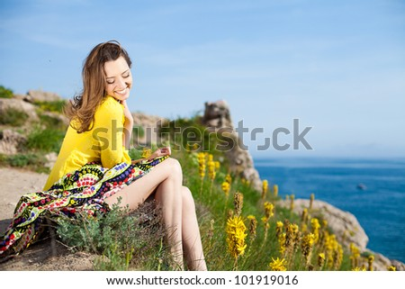 Beautiful brunette woman resting on a mountain near the sea. In summer, sunny day.