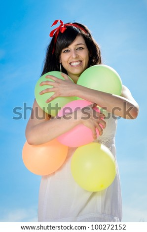 Beautiful brunette woman shows her happiness and love playing and having fun with colorful balloons. She is hugging the balloons.
