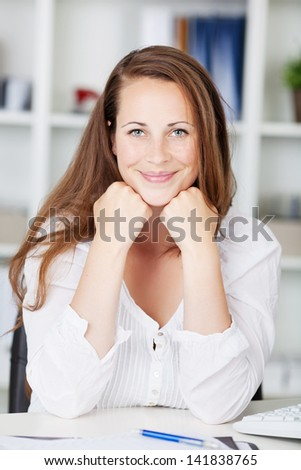 Beautiful brunette woman sitting with head resting on her hands