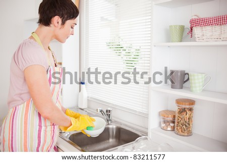Beautiful brunette woman washing the dishes in the kitchen