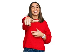 Beautiful brunette woman wearing casual winter sweater laughing at you, pointing finger to the camera with hand over body, shame expression