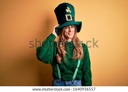 Beautiful brunette woman wearing green hat with clover celebrating saint patricks day confuse and wonder about question. Uncertain with doubt, thinking with hand on head. Pensive concept.