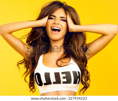 Stock Photo Beautiful brunette woman with a finger on her lips showing to keep silence, hush. Beauty girl with bright makeup hairstyle with horns in a blue dress having fun.White background, not isolate,screaming