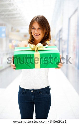 Beautiful brunette woman with a gift boxe standing inside shopping mall