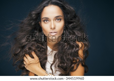 Beautiful brunette woman with beauty long curly hair and bright makeup. Fashion model with wavy hairstyle. Toned in warm colors. Studio shot, horizontal #344519960