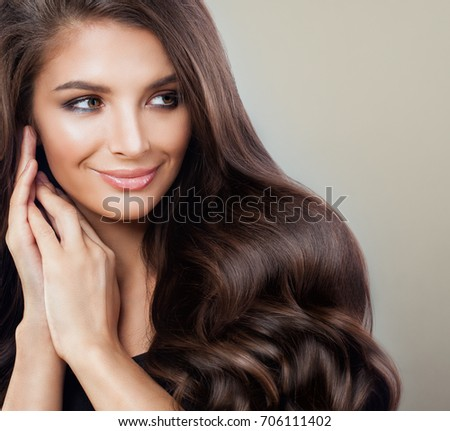 Beautiful Brunette Woman with Curly Hairstyle and Makeup, Beauty Salon or Barber Shop Background. Cute Fashion Model with  Long Healthy Hair