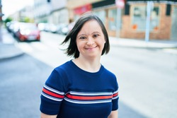 Beautiful brunette woman with down syndrome at the town on a sunny day