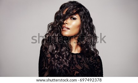 Beautiful brunette woman with long curly hair. Mixed race female with wavy hairstyle against grey background.