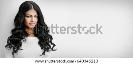 Stock Photo Beautiful brunette woman with long curly hair on white background with copy space