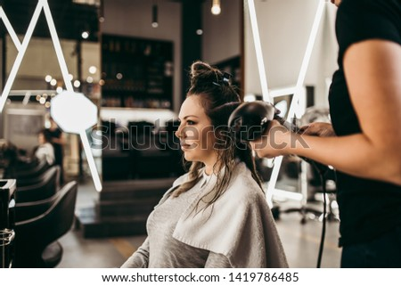 Beautiful brunette woman with long hair at the beauty salon getting a hair blowing. Hair salon styling concept. #1419786485