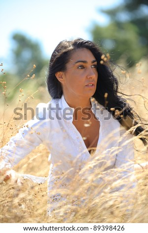 beautiful brunette woman with long hair on a field of straw wearing a white shirt thinking