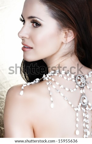 Beautiful brunette woman with white necklace on her back and soft smile - not isolated - stock photo
