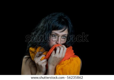 Beautiful brunette woman wrapped in a scarf with an innocent, sad expression.  On a black background with room for text.