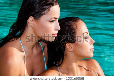 beautiful brunette women relax in pool